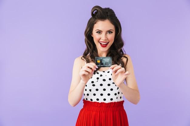 Portret radosnej kobiety pin-up w vintage sukienka w kropki uśmiecha się trzymając plastikową kartę kredytową na białym tle nad fioletową ścianą