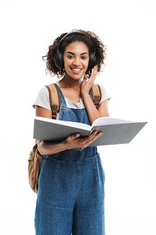 Portret radosnej kobiety słuchającej muzyki w słuchawkach podczas czytania książki odizolowanej na białej ścianie