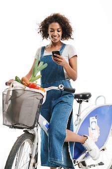 Portret radosnej kobiety trzymającej telefon komórkowy podczas jazdy na rowerze z torbą na zakupy na białym tle nad białą ścianą