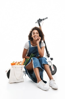 Portret radosnej kobiety uśmiechającej się siedząc na skuterze elektronicznym z torbą na zakupy na białym tle nad białą ścianą