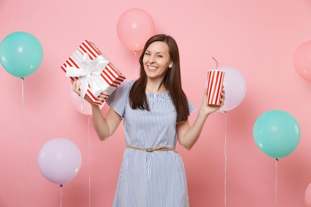 Portret radosnej kobiety w niebieskiej sukience trzymającej czerwone pudełko z prezentem i plastikowym kubkiem sody lub coli na różowym tle z kolorowymi balonami. urodziny wakacje, ludzie szczere emocje.