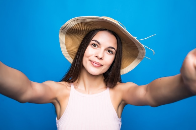 Portret radosnej kobiety w sukience i kapeluszu letnim przy selfie na białym tle nad niebieską ścianą.