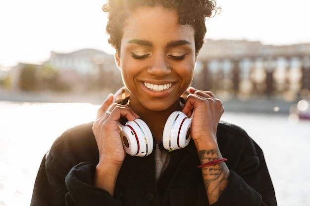 Portret radosnej kobiety z kręconą fryzurą afro trzymającą słuchawki podczas spaceru wzdłuż brzegu rzeki
