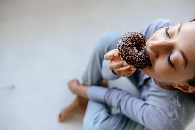 Portret radosnej kobiety zjada smaczny pączek w domu.