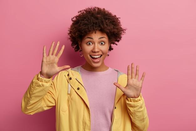 Portret radosnej kręconej kobiety z podniesionymi dłońmi, lubi wolny czas