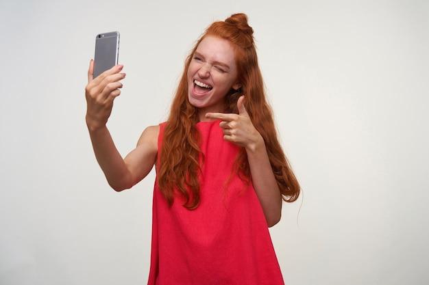 Portret radosnej młodej damy w różowej sukience, walczącej ze swoimi falistymi, lśniącymi włosami w kok, trzymającej smartfona w uniesionej ręce podczas robienia śmiesznego sellfie, wskazującej na aparat palcem wskazującym i uśmiechającej się radośnie
