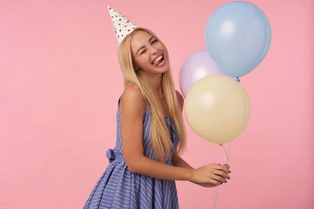 Portret radosnej młodej, długowłosej blondynki kobiety w niebieskiej letniej sukience i kapeluszu w kształcie stożka pozuje na różowym tle z wielobarwnymi balonami w dłoniach, mrugając do kamery i szczęśliwie pokazując język