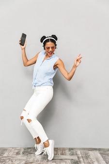 Portret radosnej młodej kobiety na białym tle okulary przeciwsłoneczne, trzymając telefon komórkowy, słuchanie muzyki w słuchawkach, taniec