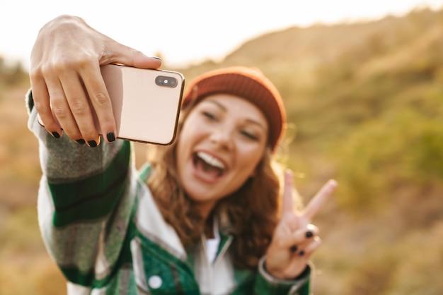 Portret radosnej młodej kobiety rasy kaukaskiej w kapeluszu i koszuli w kratę biorącej selfie portret na telefonie komórkowym podczas chodzenia na zewnątrz