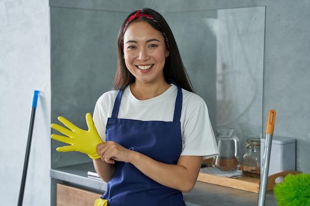 Portret radosnej młodej kobiety, sprzątaczki uśmiecha się do kamery, nosi rękawice ochronne, przygotowując się do sprzątania domu. prace domowe i sprzątanie, koncepcja usługi sprzątania