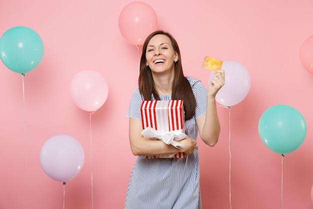 Portret radosnej młodej kobiety w niebieskiej sukience trzymającej kartę kredytową i czerwone pudełko z prezentem na pastelowym różowym tle z kolorowymi balonami. urodziny wakacje, ludzie szczere emocje.
