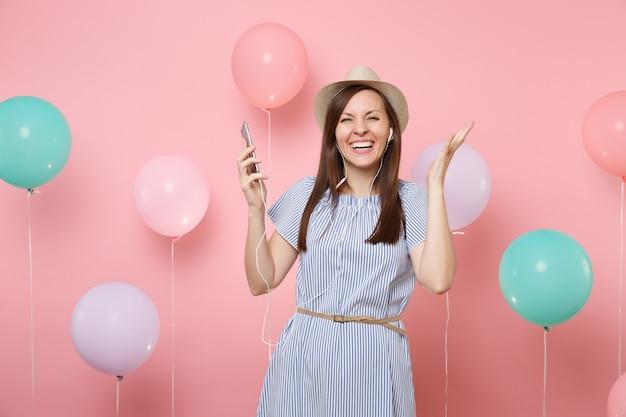 Portret radosnej młodej kobiety w słomkowym letnim kapeluszu i niebieskiej sukience z telefonem komórkowym i słuchawkami, słuchając muzyki, rozprowadzając rękę na różowym tle z kolorowymi balonami. urodzinowe przyjęcie świąteczne.