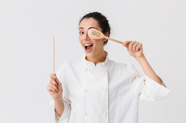 Portret radosnej młodej kobiety z naczynia kuchenne