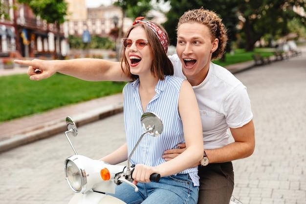 Portret radosnej młodej pary, która razem jedzie na motocyklu na ulicy miasta, wskazując palcem