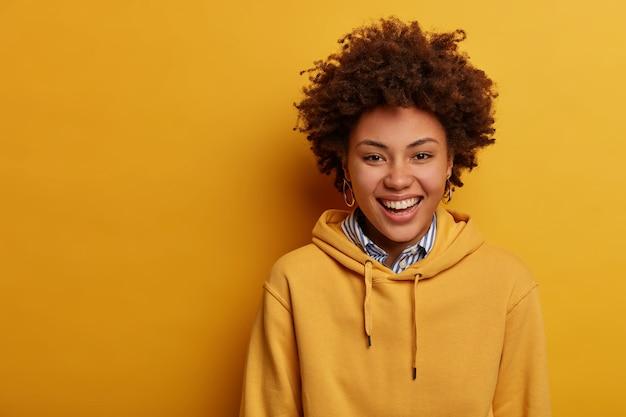 Portret radosnej nastolatki szczerze się śmieje, nosi luźną bluzę z kapturem