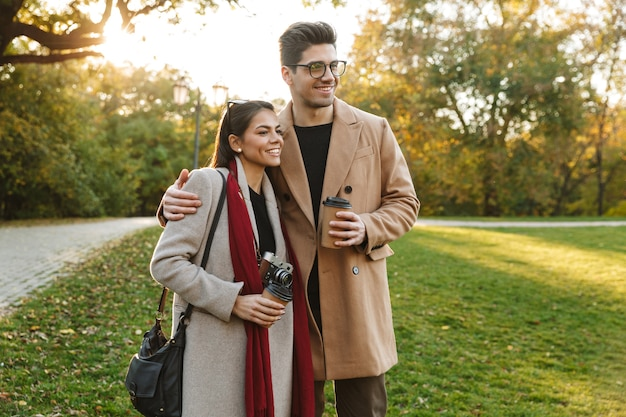 Portret radosnej pary mężczyzny i kobiety w wieku 20 lat pijących kawę na wynos z papierowych kubków podczas spaceru w jesiennym parku