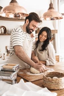 Portret radosnej pary mężczyzny i kobiety w wieku 30 lat w fartuchach mieszających ciasto podczas wspólnego gotowania w kuchni w domu
