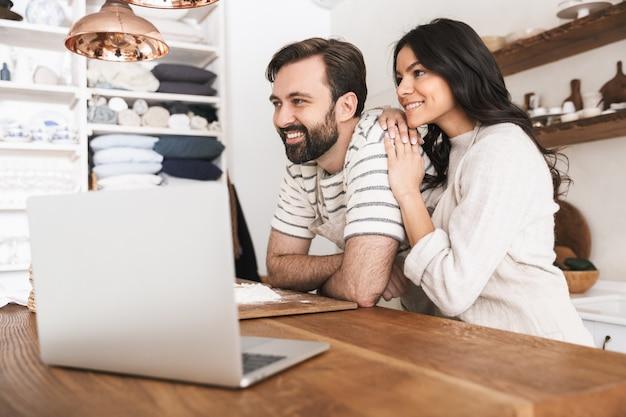 Portret radosnej pary mężczyzny i kobiety w wieku 30 lat w fartuchach, patrząc na laptopa podczas gotowania ciasta w kuchni w domu