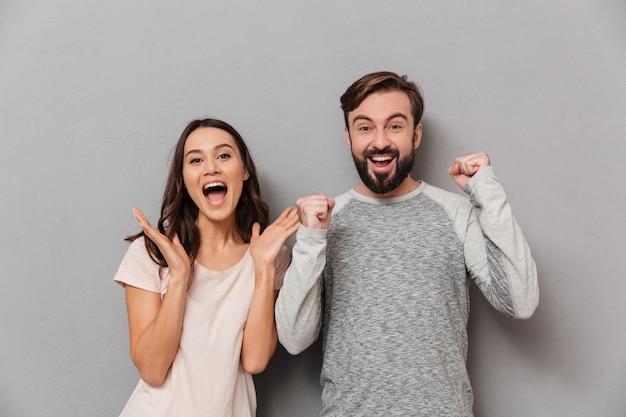 Portret radosnej pary młodych świętuje sukces