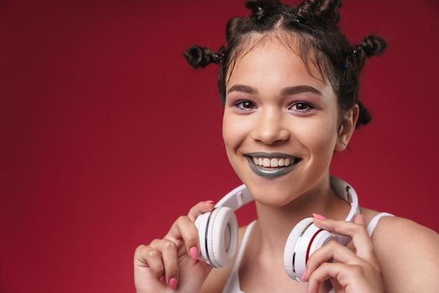 Portret radosnej punkowej dziewczyny z dziwaczną fryzurą i ciemną szminką uśmiechającą się podczas słuchania muzyki przez słuchawki izolowane nad czerwoną ścianą