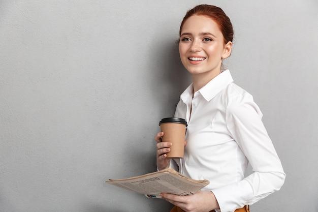 Portret radosnej rudowłosej bizneswoman 20s ubranej w strój wizytowy, pijącej kawę na wynos i czytającej gazetę w biurze na białym tle nad szarym