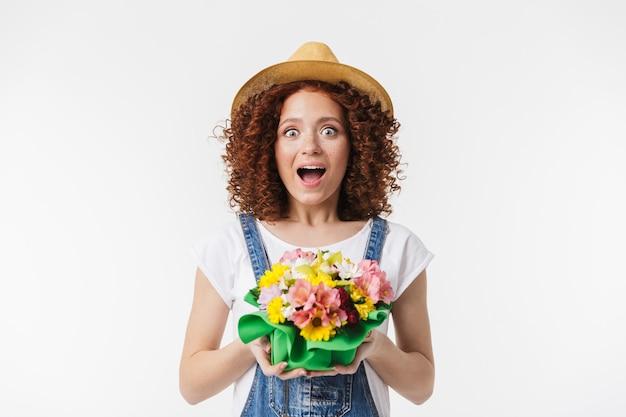 Portret radosnej rudowłosej kręconej kobiety 20s w letnim słomkowym kapeluszu uśmiechającej się i trzymającej pudełko na kwiaty izolowane nad białą ścianą