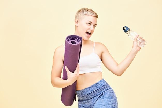 Portret radosnej, sportowej dziewczyny w stylowym stroju sportowym, wykrzykującej radosny wyraz twarzy, z szeroko otwartymi ustami, podekscytowaną przed zajęciami hatha jogi, niosącą butelkę i zwiniętą matę