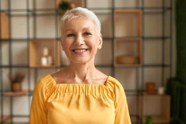 Portret radosnej stylowej kobiety w średnim wieku z krótką fryzurą, pozowanie w pomieszczeniu, wyrażając pozytywne emocje