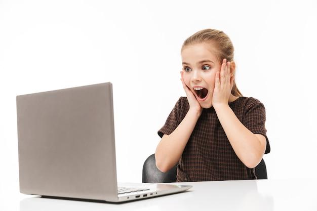 Portret radosnej uczennicy cieszącej się i używającej srebrnego laptopa siedząc przy biurku w klasie odizolowanej na białej ścianie
