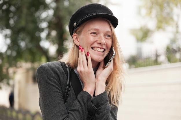 Portret radosnej uroczej młodej blondynki dzwoniącej podczas spaceru po mieście w weekendowy dzień, dotykając jej policzka uniesioną ręką i patrząc szczęśliwie przed siebie z szerokim, szczerym uśmiechem