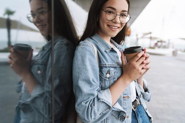 Portret radosnej uśmiechniętej nastoletniej dziewczyny w okularach trzymającej papierowy kubek kawy na wynos podczas spaceru na świeżym powietrzu