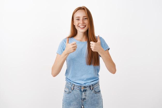 Portret radosnej, zadowolonej, dobrze wyglądającej rudowłosej kobiety z piegami pokazującymi kciuki w górę i uśmiechniętą, wspierającą i wiwatującą, udzielającą pozytywnej odpowiedzi