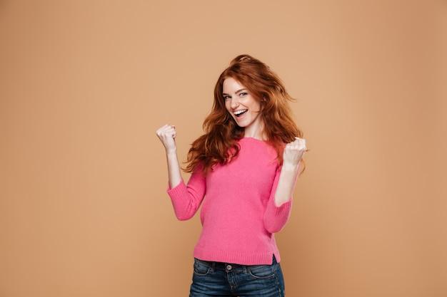 Portret radosnej zadowolony rudowłosy dziewczyna świętuje zwycięstwo