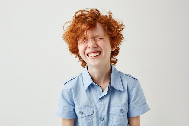 Portret radosny chłopczyk z rudymi włosami i piegami, śmiejąc się głośno z zamkniętymi oczami
