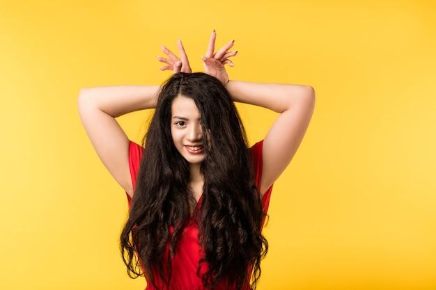 Portret radosny ładny brunetka dziewczyna z długimi włosami. śmieszna emocjonalna dama wygłupia się, robi uszy królika rękami, uśmiecha się.