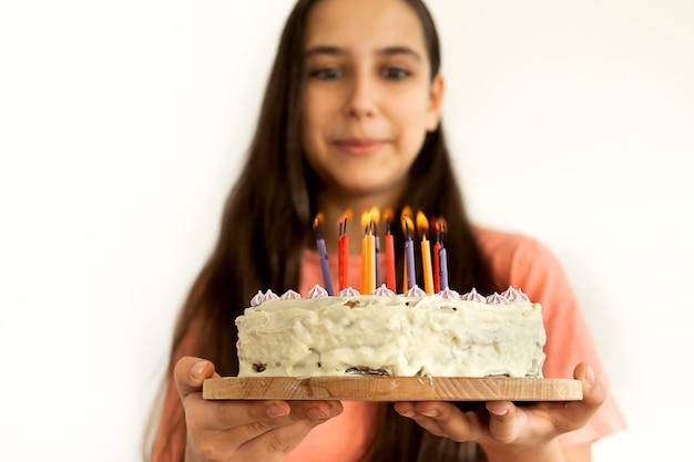 Portret radosny latin teen dziewczyna dmuchanie świeczki na tort urodzinowy. falujące przyjęcie urodzinowe w domu. tło białe ściany.