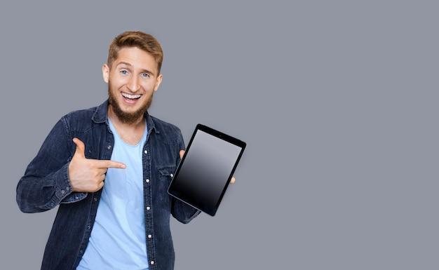 Portret radosny młody brodaty freelancer wskazując ręką na tablecie, który trzyma w ręku patrząc na aparat śmiejąc się na białym tle na szarej ścianie.