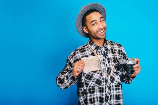 Portret radosny przystojny facet wyrażający pozytywne emocje. podróżowanie, turysta, weekendy, wakacje, turystyka, aparat fotograficzny, mapa, wesoły nastrój, uśmiech, szczęście.