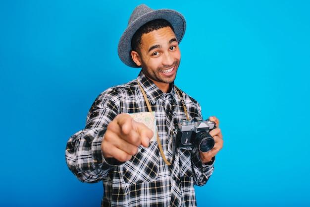 Portret radosny stylowy facet z mapy i uśmiechnięty aparat. turysta, dobra zabawa, podróże, wesoły nastrój, uśmiech, podróż, wakacje, wyrażanie prawdziwych pozytywnych emocji.