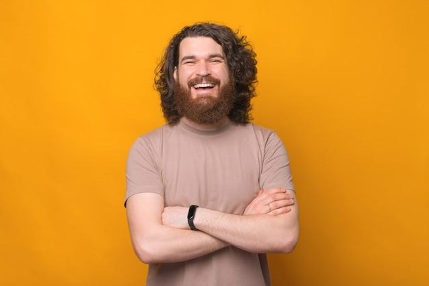 Portret radosny uśmiechnięty brodaty mężczyzna hipster ze skrzyżowanymi rękami na żółtym, patrząc na kamery