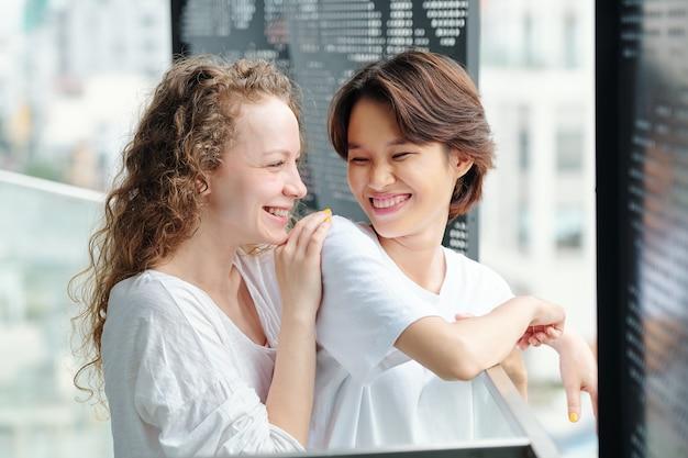 Portret radosnych, ładnych młodych kobiet, patrząc na siebie z miłością i uczuciem, stojąc rano na balkonie