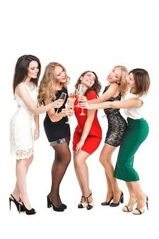 Portret radosnych przyjaciół opiekania na przyjęciu noworocznym wiele pięknych dziewczyn w sukienkach świątecznych nowego roku, uśmiechając się, bawiąc się na białym tle