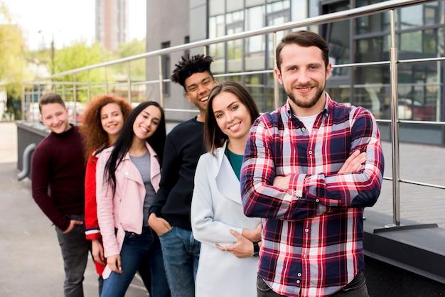 Portret radosnych przyjaciół wielorasowe stojących w rzędzie w pobliżu poręczy na ulicy