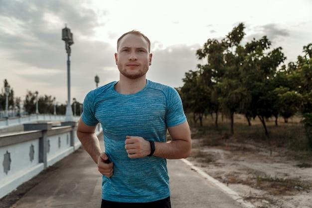 Portret rasy białej w niebieskiej koszulce i czarnych szortach, która trenuje i biegnie po asfalcie podczas zachodu słońca