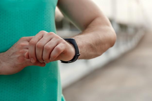 Portret rasy kaukaskiej facet w lazurowej koszulce, patrząc na odczyty fitness tracker