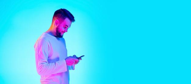 Portret rasy kaukaskiej mężczyzny na białym tle na niebieskim tle studio w świetle neonu. piękny model męski. pojęcie ludzkich emocji, wyraz twarzy, sprzedaż, reklama. copyspace dla reklamy.