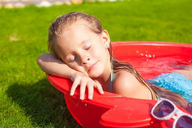 Portret relaksująca urocza mała dziewczynka cieszy się jej wakacje w małym basenie plenerowym