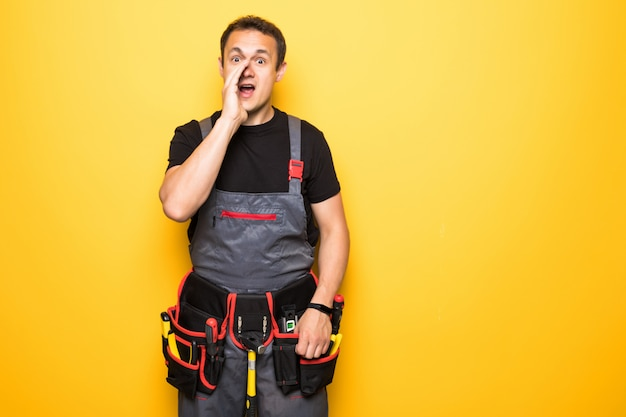 Portret repairman krzyczy podczas gdy trzymający druty przeciw żółtemu tłu