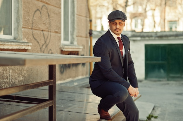 Portret retro 1920 angielski arabski biznes człowiek ubrany ciemny garnitur, krawat i kaszkiet.