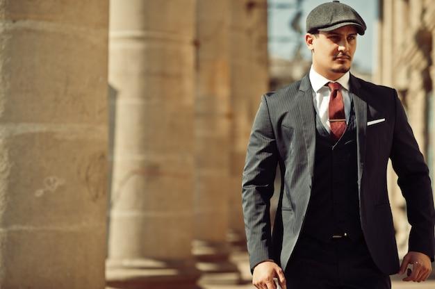 Portret retro lat 20. angielski arabski biznesmen ubrany w ciemny garnitur, krawat i kaszkiet w pobliżu starych kolumn.